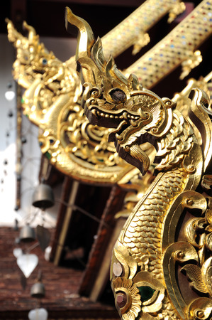 naga china: Golden dragon statues on the roof of buddhist temple in Thailand