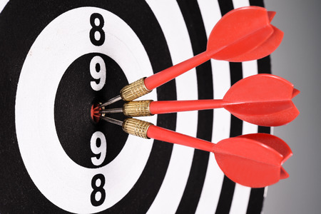 bullseye: Three red darts in the target center on gray background.