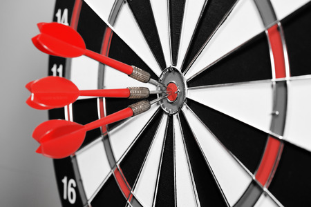 dartboard: Three red darts in the target center on gray background.