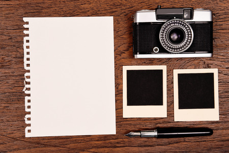 Blank notebook with pen, photo frames and camera on wooden background. photo