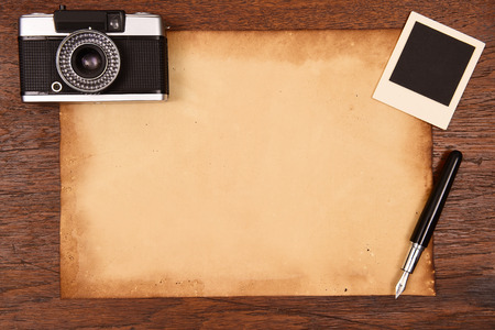 photo story: Old paper, ink pen and vintage photo frame with camera.