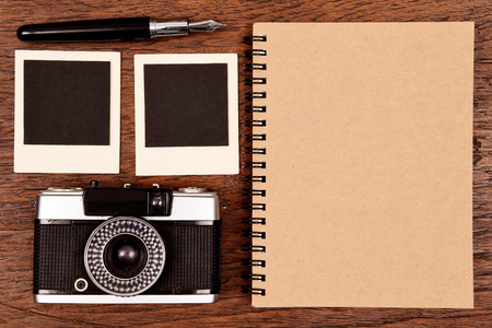 notebook with pen, photo frames and camera on wooden background. photo