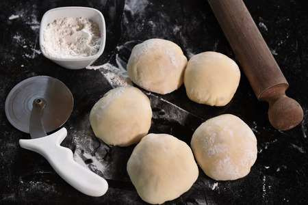 Small balls of fresh pizza dough on wooden board. photo
