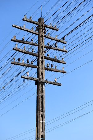 unorganized: electricity post with blue sky. Stock Photo