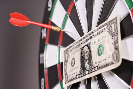 One dollar bill on a dartboard. photo