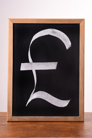 quid: pound sterling sign written with a chalk on a blackboard