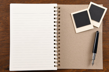 Blank notebook with pen and photo frames on wooden background. photo