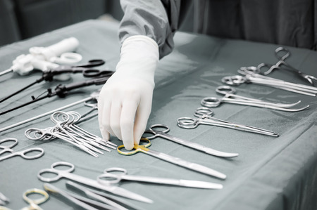 surgery room: Detail shot of steralized surgery instruments with a hand grabbing a tool ,selective color technique