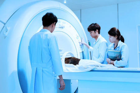veterinarian doctor working in MRI scanner room take with blue filter photo