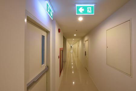 Grüne Notausgang-Zeichen, die den Weg zu entkommen Standard-Bild - 38473990