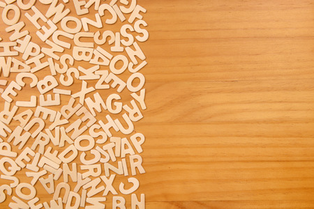 Pile of wooden letters over the wooden surface as a typography background composition photo
