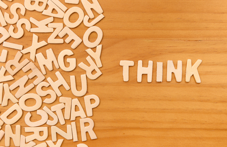 Word think made with block wooden letters next to a pile of other letters over the wooden board surface composition photo