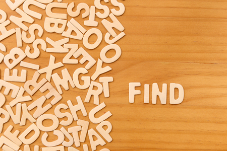 Word find made with block wooden letters next to a pile of other letters over the wooden board surface composition photo