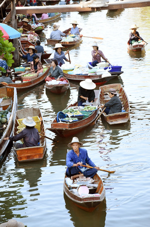 amphawa: AMPHAWA ? APRIL 29: Wooden boats are loaded with fruits from the orchards at Tha kha floating market on April 29, 2015 in Amphawa. A traditional way still practiced in Tha kha canals of Thailand.