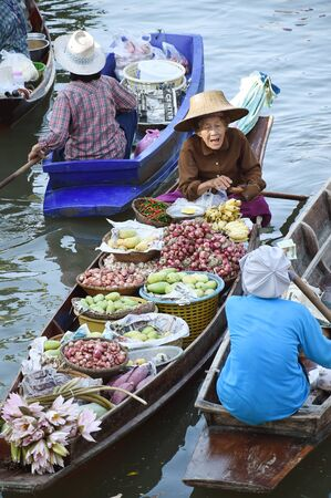 tha: AMPHAWA ? APRIL 29: Wooden boats are loaded with fruits from the orchards at Tha kha floating market on April 29, 2015 in Amphawa. A traditional way still practiced in Tha kha canals of Thailand.
