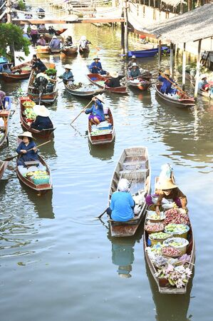 practiced: AMPHAWA ? APRIL 29: Wooden boats are loaded with fruits from the orchards at Tha kha floating market on April 29, 2015 in Amphawa. A traditional way still practiced in Tha kha canals of Thailand.