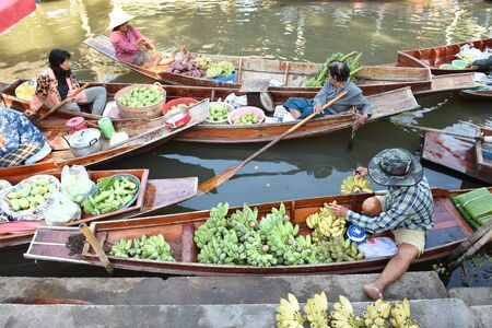 practiced: AMPHAWA  APRIL 29: Wooden boats are loaded with fruits from the orchards at Tha kha floating market on April 29 2015 in Amphawa. A traditional way still practiced in Tha kha canals of Thailand.