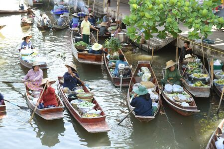 amphawa: AMPHAWA  APRIL 29: Wooden boats are loaded with fruits from the orchards at Tha kha floating market on April 29 2015 in Amphawa. A traditional way still practiced in Tha kha canals of Thailand.