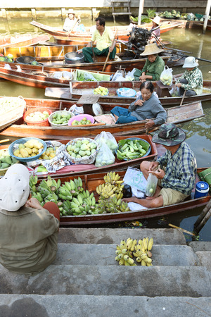 tha: AMPHAWA  APRIL 29: Wooden boats are loaded with fruits from the orchards at Tha kha floating market on April 29 2015 in Amphawa. A traditional way still practiced in Tha kha canals of Thailand.