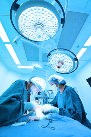 two veterinarian surgeons in operating room take with art lighting and blue filter Standard-Bild