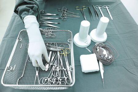 equipos medicos: Detalle de foto de instrumentos de cirugía steralized con una mano agarrando una herramienta de toma con la técnica de color selectiva y la iluminación del arte