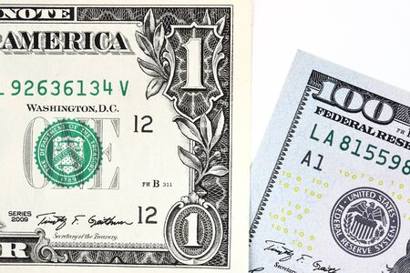 earns: Macro shot of a new 100 dollar bill and one dollar isolate on white background