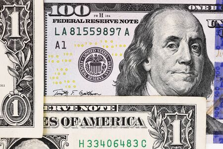 earns: Macro shot of a new 100 dollar bill and one dollar on background Stock Photo