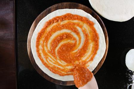 pizza base: close up of adding tomato sauce to pizza base