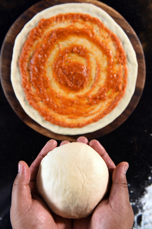 pizza base: balls of fresh pizza dough in hand and tomato sauce on pizza base