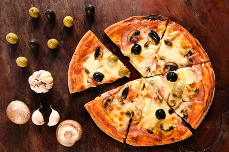 pizza and ingredients for pizza on the wooden background