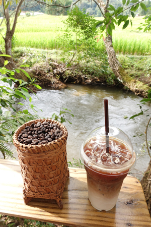 chocolate cakes: coffee cup and coffee beans on table in natural landscape view