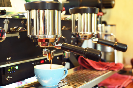 making coffee: coffee machine preparing cup of coffee. Stock Photo