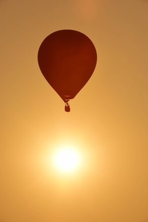 wind down: Colorful hot air balloon is flying at sunset. Stock Photo