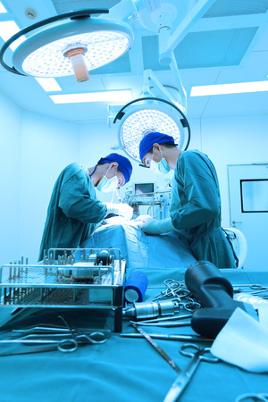 cirujano: dos cirujanos veterinarios en quirófano toman con iluminación arte y filtro azul
