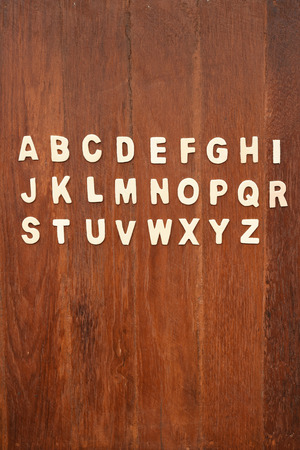 reading material: Wooden ABC letter alphabet on wooden background
