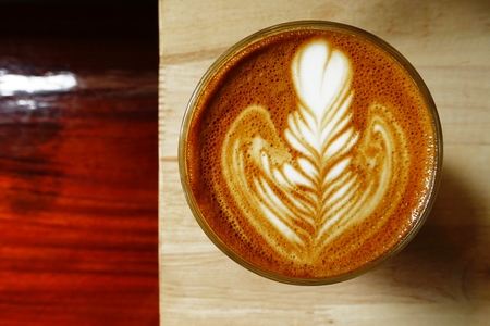 cappuccino foam: cup of latte art coffee on wooden background Stock Photo