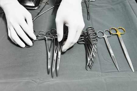 Detail shot of steralized surgery instruments with a hand grabbing a tool take with selective color technique and art lighting