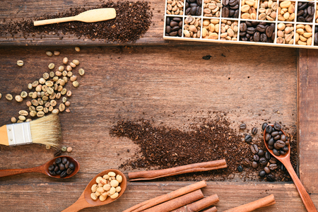 Freshly coffee beans in spoon and  ground coffee beans on table with cinnamon
