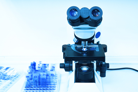 close up shot of microscope at the blood laboratory take with art lighting and blue filter