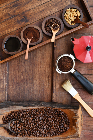 Freshly ground coffee beans in a metal filter and coffee beans with red kettle on the side. Stockfoto