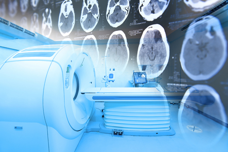 MRI scanner room with images from a computerized tomography of the brain take with art lighting and blue filter 写真素材
