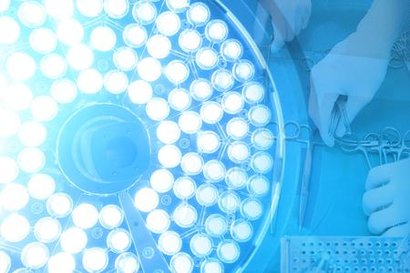 Szczegółowy strzał steralizowanych instrumentów chirurgicznych z ręką chwytającą narzędzie z lampami chirurgicznymi w sali operacyjnej z oświetleniem artystycznym i niebieskim filtrem