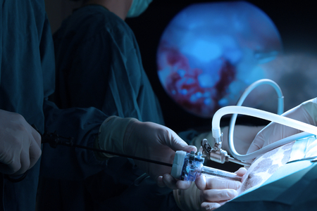 Veterinarian doctor in operation room for laparoscopic surgical take with art lighting and blue filter Stock Photo