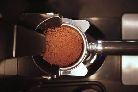 freshly ground coffee beans in a porta filter by the coffee grinder roasted make beans into a powder. Stock Photo