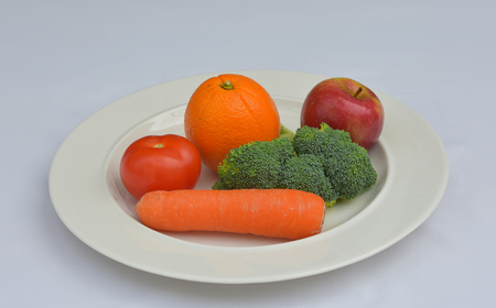 Plate showing five Fruit and Vegetables - the recommended intake for one day to maintain a healthy life