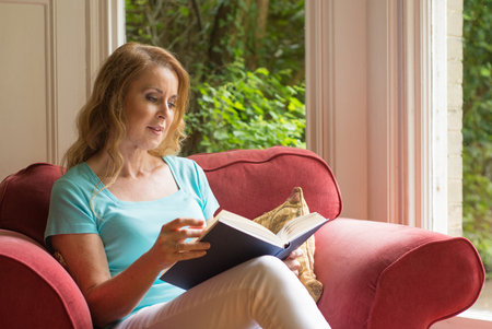 An attractive mature red headed woman in casual clothes sits and enjoys reading a book Banco de Imagens