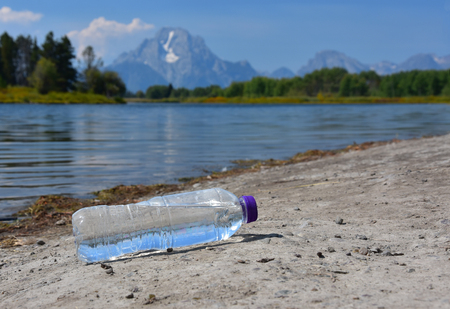 A discarded plastic bottle of water rests beside the river in a beauty spot 写真素材