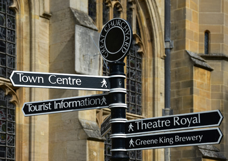 A sign in the great churchyard, with the church in the background, in Bury St Edmunds in Suffolk, East Anglia shows the way to various tourist attractions in the town. Bury St Edmunds is steeped in history and has many ancient buildings including an old abbey with beautiful gardens