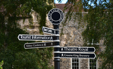 A sign in the great churchyard, with the abbey walls in the background, in Bury St Edmunds in Suffolk, East Anglia shows the way to various tourist attractions in the town. Bury St Edmunds is steeped in history and has many ancient buildings including an old abbey with beautiful gardens