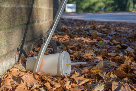 A litter picker using a tool retrieves a discarded soda cup with straw that lies amongst fallen leaves at the base of a brick wall in the autumn Banco de Imagens